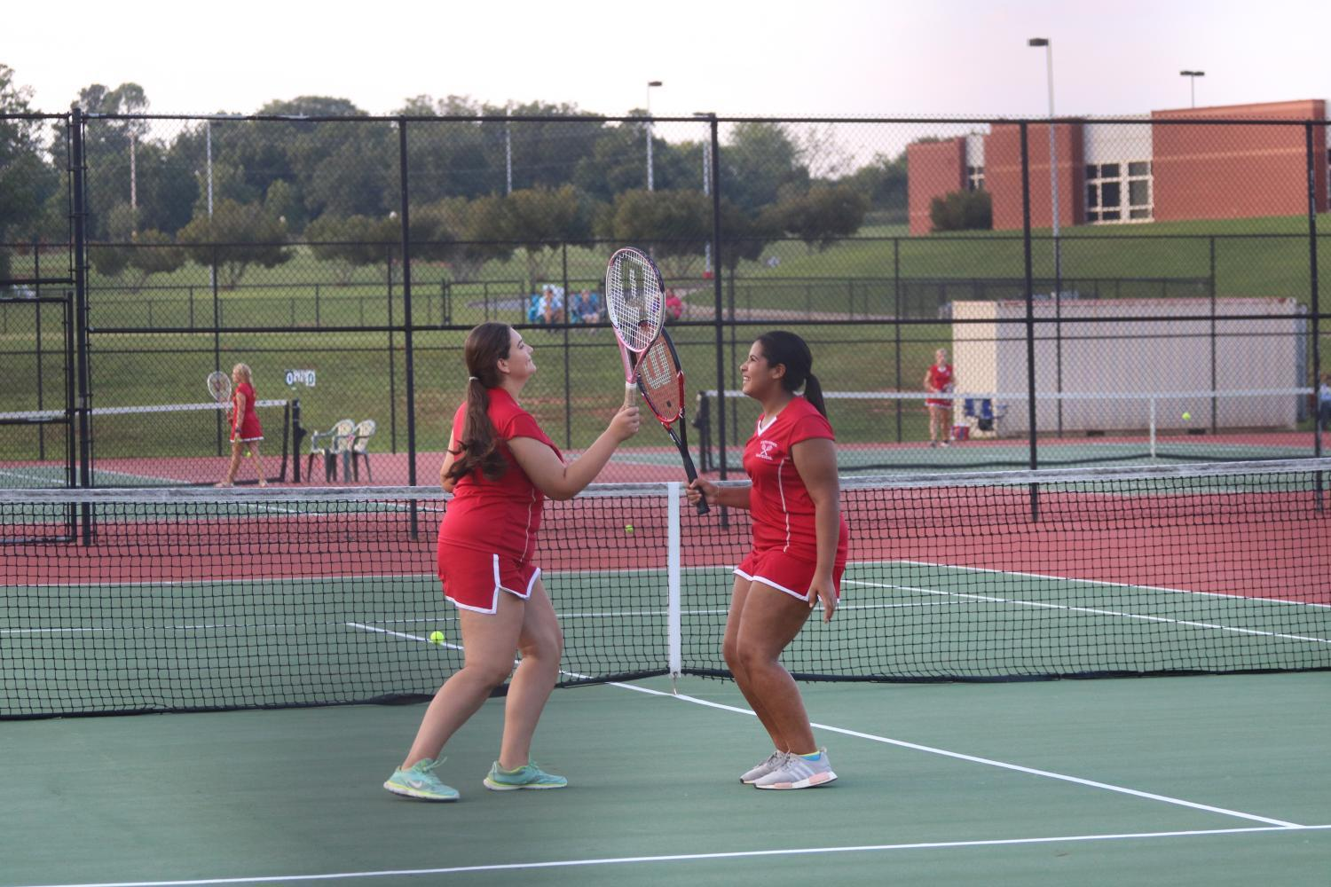 Teammates celebrate after winnning their match, playing as doubles.