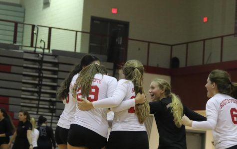 The varsity volleyball team celebrates their third and final victory against Gray Collegiate High School.