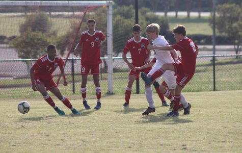Freshman, Addison Donald, successfully gets the ball away from the goal by kicking it away.